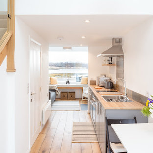 Photo of a small coastal galley open plan kitchen in Other with a single-bowl sink, shaker cabinets, grey cabinets, wood worktops, metallic splashback, integrated appliances, medium hardwood flooring, no island and brown worktops.