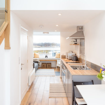 Example of a small beach style galley medium tone wood floor open concept kitchen design in Other with a single-bowl sink, shaker cabinets, gray cabinets, wood countertops, metallic backsplash, paneled appliances, no island and brown countertops
