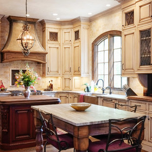 Mid-sized craftsman eat-in kitchen inspiration - Mid-sized arts and crafts l-shaped dark wood floor eat-in kitchen photo in Other with a farmhouse sink, distressed cabinets, granite countertops, beige backsplash, stone tile backsplash, paneled appliances, raised-panel cabinets and an island