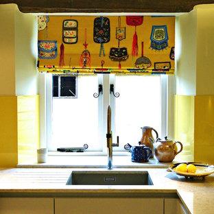 グロスタシャーの広いアジアンスタイルのおしゃれなキッチン (ドロップインシンク、フラットパネル扉のキャビネット、グレーのキャビネット、人工大理石カウンター、黄色いキッチンパネル、ガラス板のキッチンパネル、パネルと同色の調理設備、ライムストーンの床) の写真