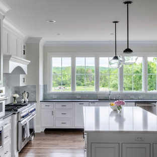Eat-in kitchen - large traditional l-shaped medium tone wood floor and brown floor eat-in kitchen idea in Cleveland with shaker cabinets, gray backsplash, subway tile backsplash, stainless steel appliances, an island, an undermount sink, white cabinets, quartz countertops and white countertops