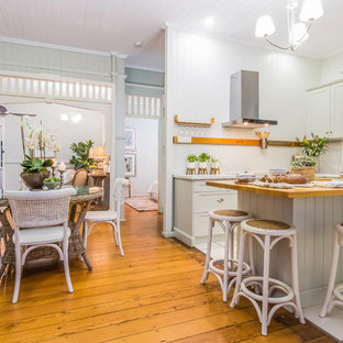 Design ideas for a country l-shaped eat-in kitchen in Brisbane with shaker cabinets, grey cabinets, wood benchtops, stainless steel appliances, medium hardwood floors, with island and brown floor.