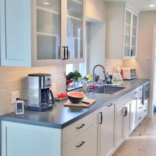 Idéer för att renovera ett avskilt, mellanstort lantligt grå grått parallellkök, med en undermonterad diskho, skåp i shakerstil, vita skåp, bänkskiva i kvarts, grått stänkskydd, stänkskydd i keramik, rostfria vitvaror, ljust trägolv och gult golv