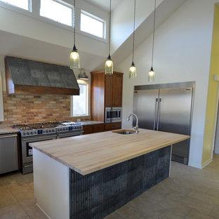 他の地域の広いモダンスタイルのおしゃれなキッチン (アンダーカウンターシンク、中間色木目調キャビネット、茶色いキッチンパネル、シルバーの調理設備、フラットパネル扉のキャビネット、木材カウンター、レンガのキッチンパネル、セラミックタイルの床) の写真