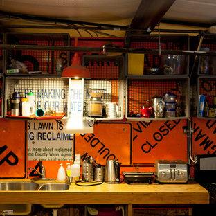 Inspiration för små industriella kök, med en undermonterad diskho, öppna hyllor, skåp i ljust trä, träbänkskiva, orange stänkskydd, stänkskydd i metallkakel, rostfria vitvaror och plywoodgolv