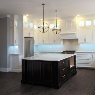 This is an example of a large traditional kitchen in Other with a farmhouse sink, flat-panel cabinets, white cabinets, stainless steel appliances, with island, pink floor and white benchtop.