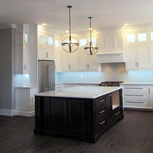 Foto de cocina clásica, grande, con fregadero sobremueble, armarios con paneles lisos, puertas de armario blancas, electrodomésticos de acero inoxidable, una isla, suelo rosa y encimeras blancas