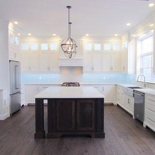 Foto de cocina tradicional, grande, con fregadero sobremueble, armarios con paneles lisos, puertas de armario blancas, electrodomésticos de acero inoxidable, una isla, suelo rosa y encimeras blancas