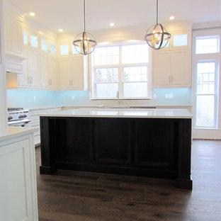 Ejemplo de cocina clásica, grande, con fregadero sobremueble, armarios con paneles lisos, puertas de armario blancas, electrodomésticos de acero inoxidable, una isla, suelo rosa y encimeras blancas