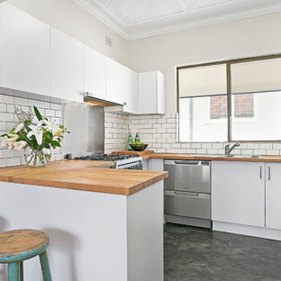 Mid-sized contemporary u-shaped separate kitchen in Sydney with a double-bowl sink, white cabinets, wood benchtops, white splashback, subway tile splashback, stainless steel appliances, vinyl floors, flat-panel cabinets and a peninsula.