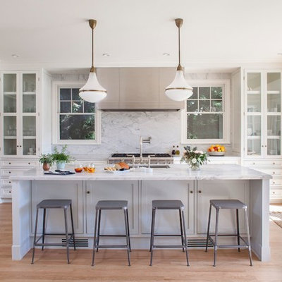 Example of a mid-sized transitional l-shaped light wood floor eat-in kitchen design in Los Angeles with an undermount sink, glass-front cabinets, white cabinets, marble countertops, white backsplash, stone slab backsplash, stainless steel appliances and an island