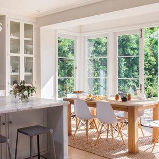 Zweizeilige, Mittelgroße Klassische Wohnküche mit hellem Holzboden, Unterbauwaschbecken, Glasfronten, weißen Schränken, Marmor-Arbeitsplatte, Küchenrückwand in Weiß, Rückwand aus Stein, Küchengeräten aus Edelstahl und Kücheninsel in Los Angeles