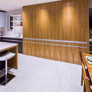 Imagen de cocina comedor en U, actual, de tamaño medio, con armarios con paneles lisos, puertas de armario grises, encimera de acrílico, salpicadero blanco, salpicadero de azulejos tipo metro, electrodomésticos de acero inoxidable, una isla y suelo de terrazo