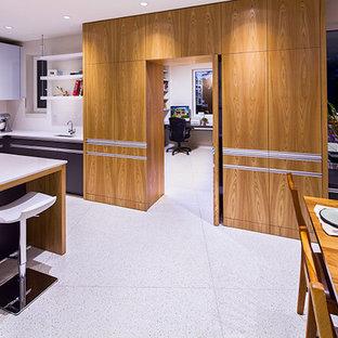 Diseño de cocina comedor en U, contemporánea, de tamaño medio, con armarios con paneles lisos, puertas de armario grises, encimera de acrílico, salpicadero blanco, salpicadero de azulejos tipo metro, electrodomésticos de acero inoxidable, una isla y suelo de terrazo