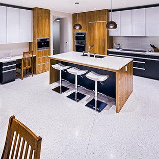 Ejemplo de cocina comedor en L, minimalista, de tamaño medio, con fregadero bajoencimera, armarios con paneles lisos, puertas de armario blancas, encimera de acrílico, salpicadero blanco, salpicadero de azulejos tipo metro, electrodomésticos de acero inoxidable, una isla y suelo de terrazo