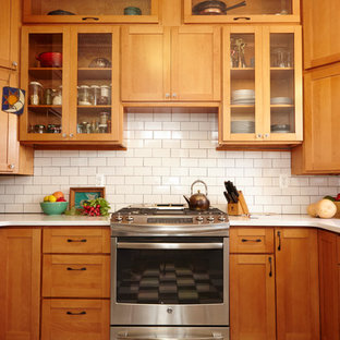 Photo of a mid-sized arts and crafts u-shaped separate kitchen in New York with an undermount sink, shaker cabinets, medium wood cabinets, quartz benchtops, white splashback, ceramic splashback, stainless steel appliances, ceramic floors and no island.