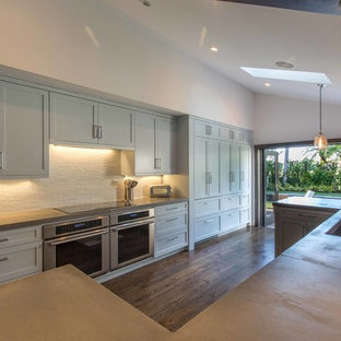 Large eclectic kitchen pictures - Large eclectic u-shaped medium tone wood floor kitchen photo in Miami with a single-bowl sink, shaker cabinets, blue cabinets, concrete countertops, white backsplash, glass tile backsplash, paneled appliances and a peninsula