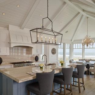 Bild på ett mycket stort maritimt beige beige kök och matrum, med luckor med infälld panel, vita skåp, marmorbänkskiva, beige stänkskydd, stänkskydd i marmor, rostfria vitvaror, mellanmörkt trägolv och en köksö