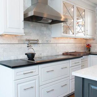 Inspiration for a small traditional l-shaped separate kitchen in Philadelphia with a farmhouse sink, white cabinets, soapstone benchtops, panelled appliances, medium hardwood floors, with island, multi-coloured floor and black benchtop.