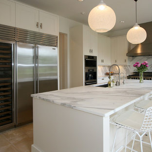 Example of a trendy l-shaped kitchen design in New Orleans with an undermount sink, recessed-panel cabinets, white cabinets, white backsplash and stainless steel appliances