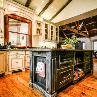 サンフランシスコの広いトラディショナルスタイルのおしゃれなキッチン (ドロップインシンク、フラットパネル扉のキャビネット、淡色木目調キャビネット、御影石カウンター、黒いキッチンパネル、大理石のキッチンパネル、シルバーの調理設備、無垢フローリング、茶色い床) の写真