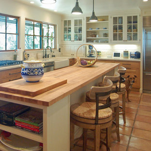 Large mediterranean enclosed kitchen inspiration - Enclosed kitchen - large mediterranean l-shaped terra-cotta tile enclosed kitchen idea in San Luis Obispo with a farmhouse sink, beaded inset cabinets, white cabinets, marble countertops, white backsplash, stone tile backsplash, stainless steel appliances and an island