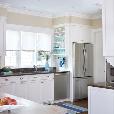 Inspiration for a large timeless l-shaped medium tone wood floor and brown floor kitchen remodel in Chicago with an undermount sink, recessed-panel cabinets, white cabinets, granite countertops, white backsplash, subway tile backsplash, stainless steel appliances and brown countertops