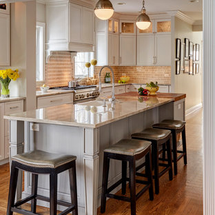 Transitional enclosed kitchen ideas - Transitional galley medium tone wood floor and brown floor enclosed kitchen photo in Chicago with a farmhouse sink, shaker cabinets, white cabinets, beige backsplash, subway tile backsplash, an island and beige countertops