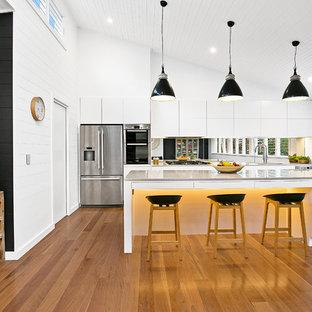 シドニーのコンテンポラリースタイルのおしゃれなキッチン (ドロップインシンク、フラットパネル扉のキャビネット、白いキャビネット、ミラータイルのキッチンパネル、シルバーの調理設備の、無垢フローリング) の写真