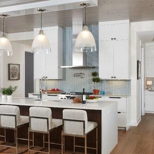 Ispirazione per una grande cucina minimal con lavello sottopiano, ante lisce, ante bianche, top in superficie solida, paraspruzzi blu, pavimento in legno massello medio, isola, elettrodomestici da incasso, paraspruzzi con piastrelle in ceramica, pavimento marrone e top bianco