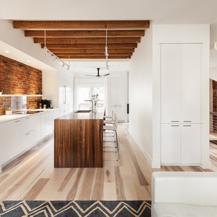 Large contemporary eat-in kitchen appliance - Large trendy single-wall light wood floor eat-in kitchen photo in Boston with an undermount sink, flat-panel cabinets, white cabinets, wood countertops, red backsplash, glass sheet backsplash, white appliances and an island