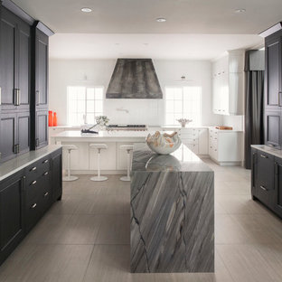 Large trendy porcelain floor and beige floor kitchen photo in Orlando with an undermount sink, black cabinets, stainless steel appliances, two islands and recessed-panel cabinets