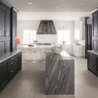 Imagen de cocina actual, grande, con fregadero bajoencimera, puertas de armario negras, electrodomésticos de acero inoxidable, dos o más islas, armarios con paneles empotrados, suelo de baldosas de porcelana y suelo beige