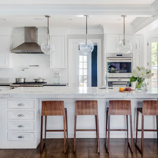 Large transitional kitchen pictures - Large transitional l-shaped brown floor and dark wood floor kitchen photo in Boston with a single-bowl sink, white cabinets, white backsplash, stone tile backsplash, stainless steel appliances, an island, shaker cabinets and marble countertops