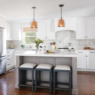 Foto på ett maritimt vit l-kök, med skåp i shakerstil, vita skåp, bänkskiva i kvarts, vitt stänkskydd, stänkskydd i marmor, rostfria vitvaror, mellanmörkt trägolv, brunt golv och en köksö