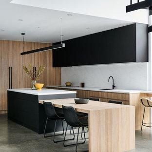 Стильный дизайн: маленькая угловая кухня в современном стиле с обеденным столом, врезной раковиной, светлыми деревянными фасадами, столешницей из кварцевого агломерата, белым фартуком, фартуком из кварцевого агломерата, техникой из нержавеющей стали, бетонным полом, островом, серым полом и белой столешницей - последний тренд