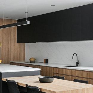 На фото: маленькая угловая кухня в современном стиле с обеденным столом, врезной раковиной, светлыми деревянными фасадами, столешницей из кварцевого агломерата, белым фартуком, фартуком из кварцевого агломерата, техникой из нержавеющей стали, бетонным полом, островом, серым полом и белой столешницей с