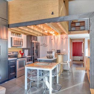 ワシントンD.C.の大きいインダストリアルスタイルのおしゃれなキッチン (アンダーカウンターシンク、シェーカースタイル扉のキャビネット、グレーのキャビネット、クオーツストーンカウンター、黄色いキッチンパネル、シルバーの調理設備の、磁器タイルの床、グレーの床、白いキッチンカウンター) の写真
