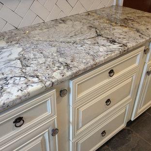 Inspiration for a traditional kitchen in Nashville with raised-panel cabinets, white cabinets, granite benchtops, white splashback, porcelain splashback and slate floors.