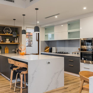 This is an example of a contemporary eat-in kitchen in Perth with flat-panel cabinets, grey cabinets, grey splashback, glass sheet splashback, stainless steel appliances, light hardwood floors, a peninsula, beige floor and grey benchtop.