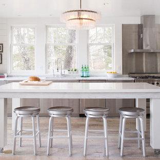Immagine di una cucina chic di medie dimensioni con ante lisce, ante in acciaio inossidabile, top in marmo, elettrodomestici in acciaio inossidabile, isola, lavello sottopiano, paraspruzzi a effetto metallico e pavimento in legno massello medio