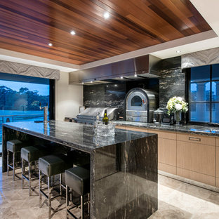 Photo of a contemporary galley open plan kitchen in Perth with flat-panel cabinets, light wood cabinets, black splashback, stone slab splashback, stainless steel appliances and with island.