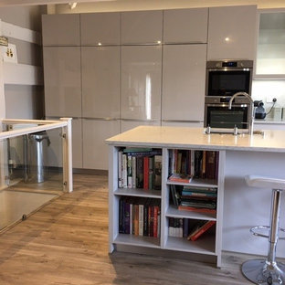 Photo of a mid-sized contemporary single-wall open plan kitchen in Oxfordshire with an integrated sink, flat-panel cabinets, beige cabinets, solid surface benchtops, grey splashback, stone slab splashback, panelled appliances, laminate floors and with island.