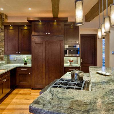 Kitchen - rustic u-shaped medium tone wood floor kitchen idea in Denver with recessed-panel cabinets, dark wood cabinets, stainless steel appliances, an island, an undermount sink, granite countertops, gray backsplash and stone tile backsplash