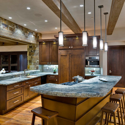 Inspiration for a large rustic medium tone wood floor eat-in kitchen remodel in Denver with an undermount sink, recessed-panel cabinets, dark wood cabinets, granite countertops, gray backsplash, stone tile backsplash, stainless steel appliances and an island