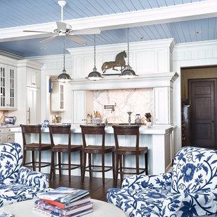 Modelo de cocina tradicional, abierta, con armarios con paneles empotrados, puertas de armario blancas, salpicadero blanco, electrodomésticos con paneles y salpicadero de mármol