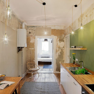 Esempio di una cucina industriale di medie dimensioni con lavello da incasso, top in legno, paraspruzzi verde e pavimento in legno massello medio