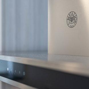 バンクーバーの中サイズのコンテンポラリースタイルのおしゃれなキッチン (アンダーカウンターシンク、フラットパネル扉のキャビネット、茶色いキャビネット、クオーツストーンカウンター、白いキッチンパネル、磁器タイルのキッチンパネル、シルバーの調理設備、磁器タイルの床、アイランドなし、白い床、グレーのキッチンカウンター) の写真
