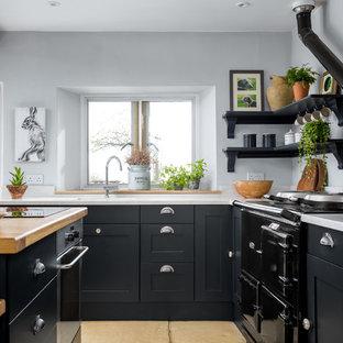 グロスタシャーの中サイズのカントリー風おしゃれなキッチン (落し込みパネル扉のキャビネット、黒いキャビネット、一体型シンク、ベージュの床、白いキッチンカウンター) の写真