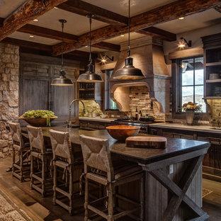 Rustik inredning av ett l-kök, med en köksö, brunt golv, en rustik diskho, luckor med infälld panel, skåp i mörkt trä, grått stänkskydd, integrerade vitvaror och mörkt trägolv